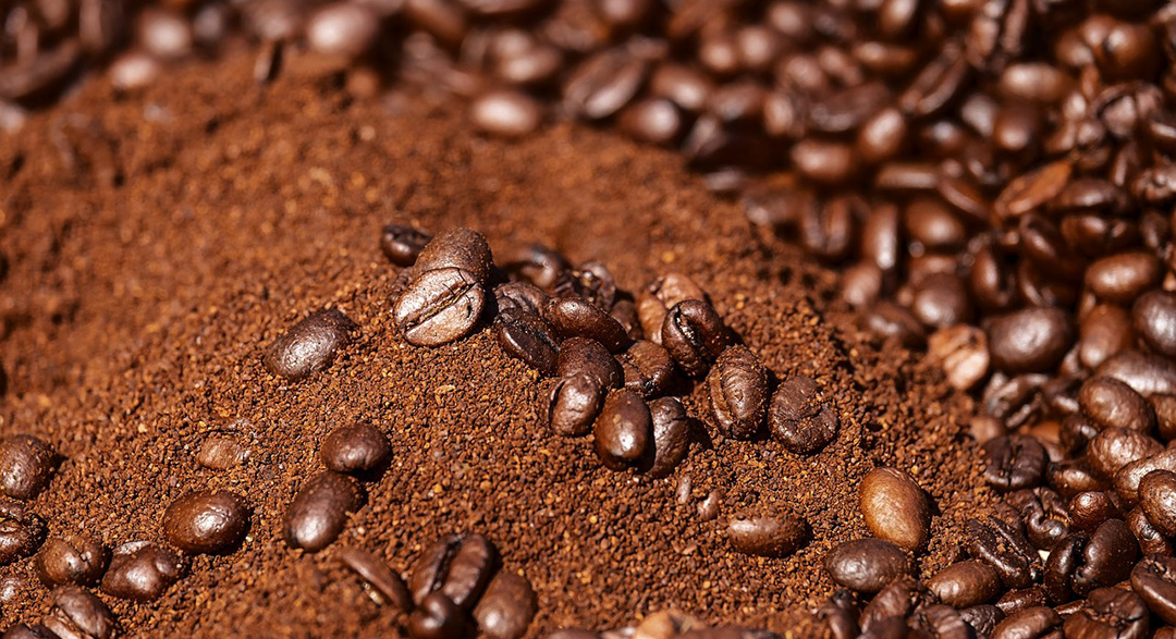 Pile of coffee beans and coffee grounds