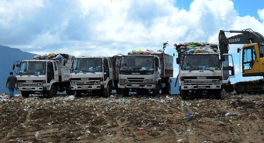 Four dump trucks on a landfill in a developing country