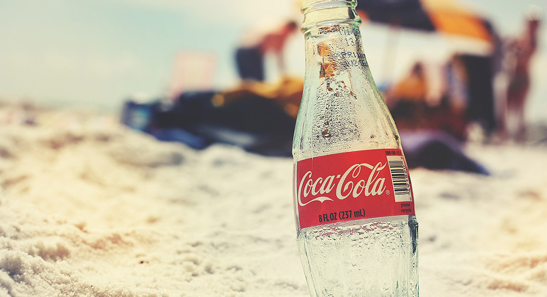 Glass of cold Coca-Cola on a beach under the sun