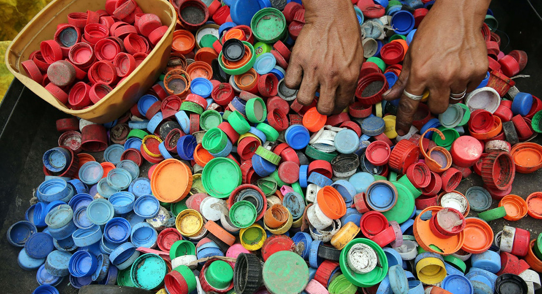 Person sorts plastic bottle caps for recycling rates