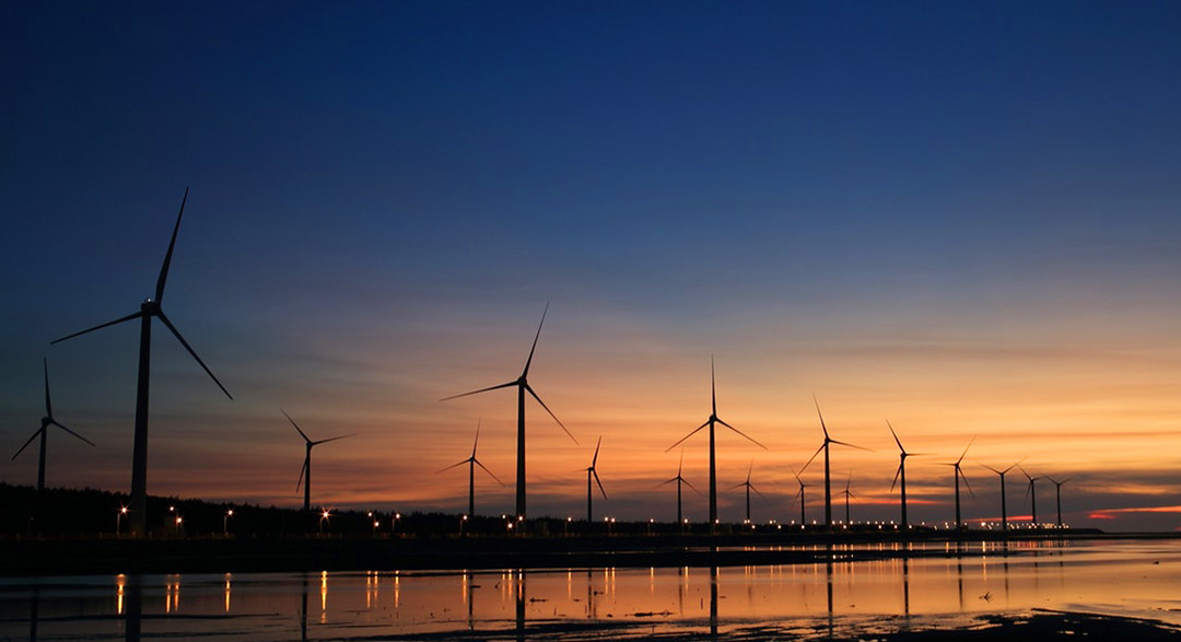 Renewable wind energy turbines at sunset