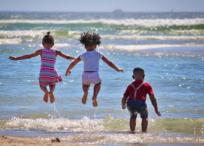 Three children jump in clean environment