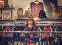 Girl peruses clothing at thrift shop