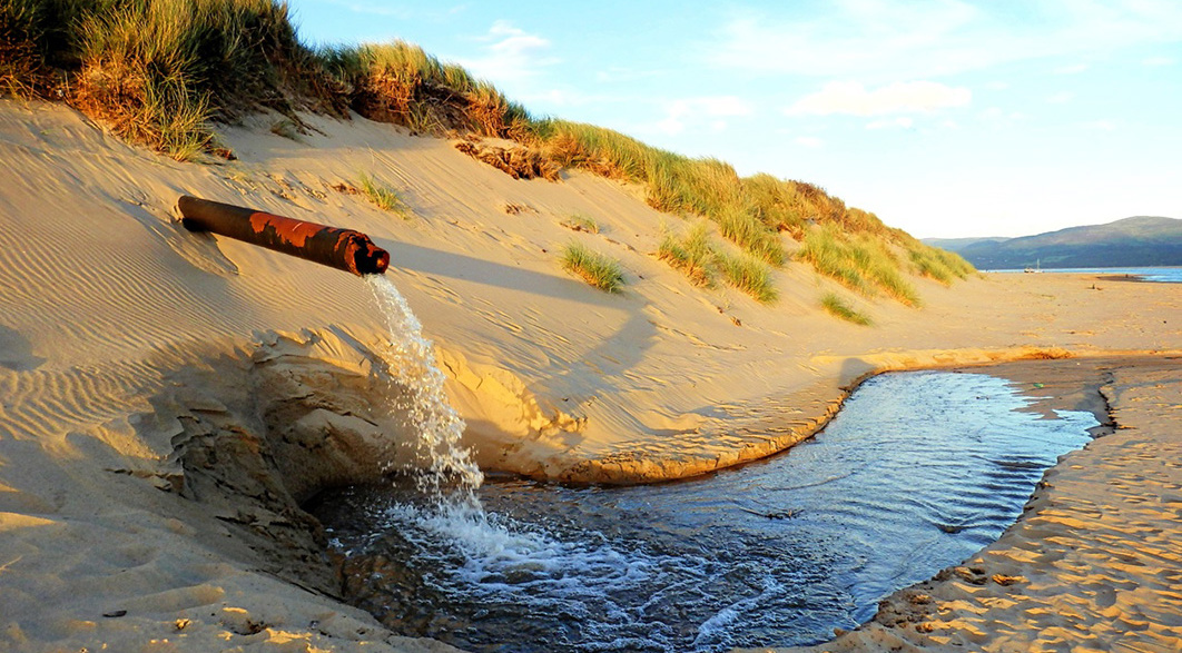 Wastewater flows from pipe onto beach sand