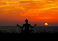 Silhouette of person meditating at sunset